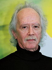 An elderly Caucasian man with a gray mustache and gray receding hair faces the camera with a neutral expression.