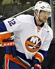 Josh Bailey in a white away Islanders jersey with a white helmet on, holding his hockey stick
