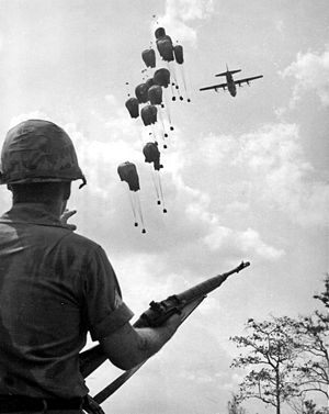 Weapons of the Vietnam War - A U.S. soldier with an M14 watches as supplies are dropped in Vietnam, 1967.