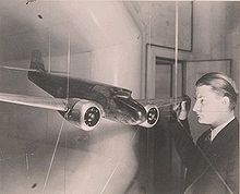 Kelly Johnson facing a model of the Lockheed Model 10 Electra, whose design he worked on. A wind tunnel opening is just behind the model.