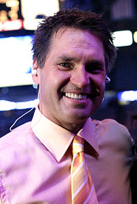Kelly Hrudey smiling in a pink button-up shirt with a tie on