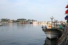 Due barche ancorano in un porto sulla destra.  Il cielo azzurro e il mare sono limpidi e tranquilli.