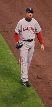 "A man in a grey baseball uniform with the word ""BOSTON"" written across the chest in red letters walks along a baseball field."