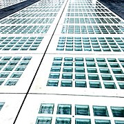 A close-up of a similar grid of glass squares, slightly blueish glass with a wavy lower surface, in full sunlight.