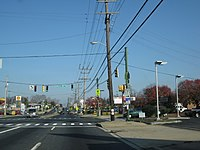 A four lane divided highway in a commercial area at a traffic light. On the traffic light pole, a Maryland Route 171 shield with a right arrow can be seen.