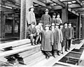 Men in suits standing on boards amidst the steel frame of the tower at the Smith Tower construction site, Seattle, Washington (SEATTLE 4896).jpg
