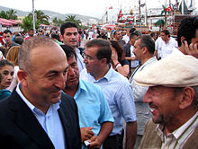 Two older Turkish men stand facing each other, one bald, the other wearing a white cap, while a large crowd mingles behind them along a waterfront.