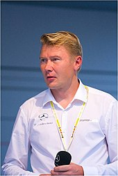 Head and shoulders of a man in his forties with blonde hair and grey eyes. He is wearing a white shirt which bears the Mercedes-Benz and AMG logos, and is holding a microphone in both of his hands.