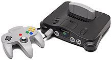 The Nintendo 64 controller is light gray controller with three handles for the player's two hands. It has red, green, blue, and yellow buttons, an analog stick, and a directional pad. The controller is plugged into the charcoal gray Nintendo 64 with a light gray cartridge inserted. The sleek console is convex on its top, and has two power switches and four controller ports.