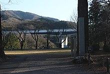 画像左 :長篠城址から望む新東名の長篠城大橋。画像右:周辺景観、地域の歴史に配慮して波形鋼板を長篠城の瓦をイメージした黒に塗装[273]。