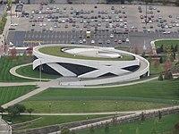 Letecký pohled na kulaté bílé muzeum s travnatou střechou a důvody