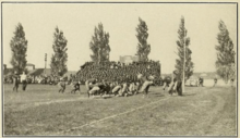 A tan and black blurry picture of two groups of men playing football with little protective equipment
