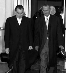 Photographie de deux hommes portant de longues manteaux quittant un bâtiment