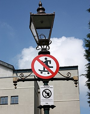 Street skateboarding - A street lamp with a sign prohibiting skateboarding.