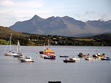 A body of water in the foreground contains several sailing vessels, including yachts, small fishing boats and an orange lifeboat. In the middle distance a variety of modern cottages are set amongst coniferous trees on a long grassy slope. Large and precipitous black mountains dominate the background.