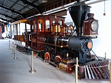 A red steam locomotive with a 0-4-2T wheel arrangement (no leading wheels, four driving wheels, and two trailing wheels) and no tender, coupled to a small train car