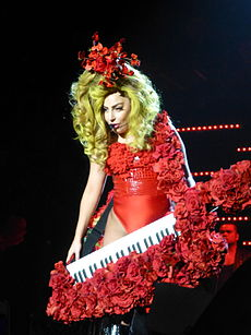 With long blonde hair, a woman holds an instrument wearing a red outfit.