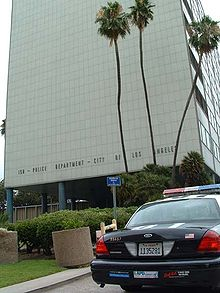 "A tall light-colored modernist building with three tall palm trees in front of it and the words ""150 – Police Department City of Los Angeles"" in capital letters near the bottom. The rear of a parked police car is visible at bottom right"