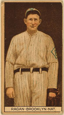 A sepia-toned baseball card image of a man in an old-style white pinstriped baseball uniform and cap