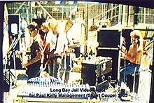 Kelly trentenne è mostrata nel profilo sinistro mentre suona una chitarra davanti a un microfono.  Alla sua destra ci sono due chitarristi e un tastierista tra apparecchiature musicali.  Dietro la tastiera c'è il batterista al suo kit, parzialmente oscurato da un altro microfono.  Sullo sfondo ci sono alte recinzioni.