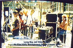 Thirty year old Kelly is shown in left profile playing a guitar in front of a microphone. To his right are two guitarists and a keyboardist amid musical equipment. Behind the keyboard is the drummer at his kit, partly obscured by another microphone. In the background are high fences.