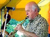 A man wearing a patterned dress shirt, performing a wind instrument while standing behind a microphone