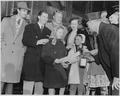 Photograph of Margaret O'Brien signing an autograph while Zachary Scott, Eddie Bracken, Van Johnson, Diana Lynn, and... - NARA - 199315.tif