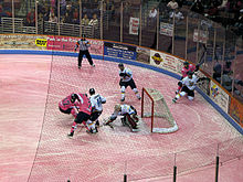 South Carolina Stingrays (in pink jerseys) battle the Toledo Walleye (in white jerseys) for control of the puck in front of the Walleye goaltender. The ice is dyed pink for Pink in the Rink 2010.