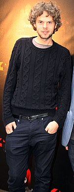 Three-quarter body shot of a 33-year-old man. He stands facing the camera with his right shoulder raised and hands placed into his jeans' pockets. He wears a dark jumper over a pale tee-shirt. His brown hair is slightly curly and about collar length. He has a slight beard.