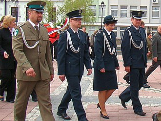 Law enforcement in Poland - An officer of the Straż Graniczna (Border Guard) in parade uniform walks with colleagues from the Służba Celna (Customs Service)
