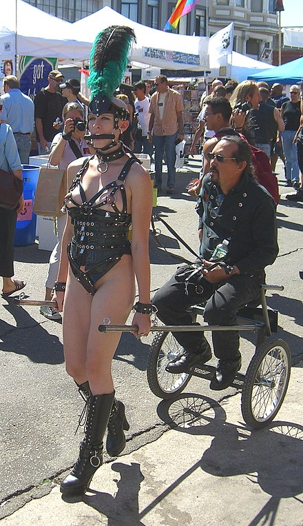 A sulky cart drawn by a pony-girl, an example of petplay at the Folsom Parade, 2005. She is wearing a bit gag and a neck collar, to which are attached a ring of O and a leash. To her nipples are attached bells. All these symbols are indicative of her roleplaying a BDSM pet slave. Ponygirl folsom2005.jpg