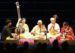 A mixed-gender group of five people sits on a platform, two playing long-necked lutes, another two playing bowed instruments, and one resting his hands next to drums.