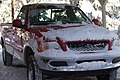 Red Ford F-150 covered partially in snow (5311459472).jpg