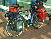 Touring bicycle equipped with head lamp, pump, rear rack, fenders/mud-guards, water bottles and cages, and numerous saddle-bags.