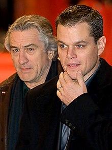 Foto van Damon en De Niro, elanden Draagt Een roken jas en Een donker blauw shirt.