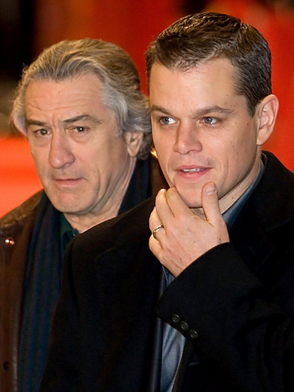 Photo of Damon and De Niro, each wearing a tuxedo jacket and a dark blue shirt.