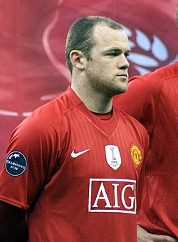 A man named Wayne Rooney lining up wearing Manchester United's jersey; the FIFA Club World Cup badge is clearly visible on the jersey.