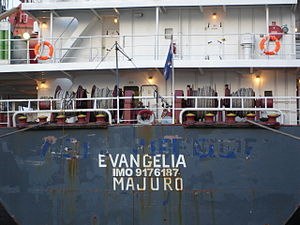 "IMO number - Stern of ""Evangelia"" displaying ""IMO 9176187"" and port of registry (""Majuro""). In addition to the current name parts of the ship's former names are visible: ""Cornelie Oldendorff"" and ""Asia Melody"". The ship's current name is ""Evangelia"" (as of 2007)"
