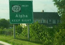 A green sign on the side of the road reading Route 122 west Alpha keep right