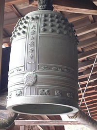 A large, greenish-grey bell hangs from a beamed wooden ceiling