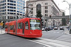 A red streetcar on a single track crosses a city street, with cars stopped in the background under a monorail track.