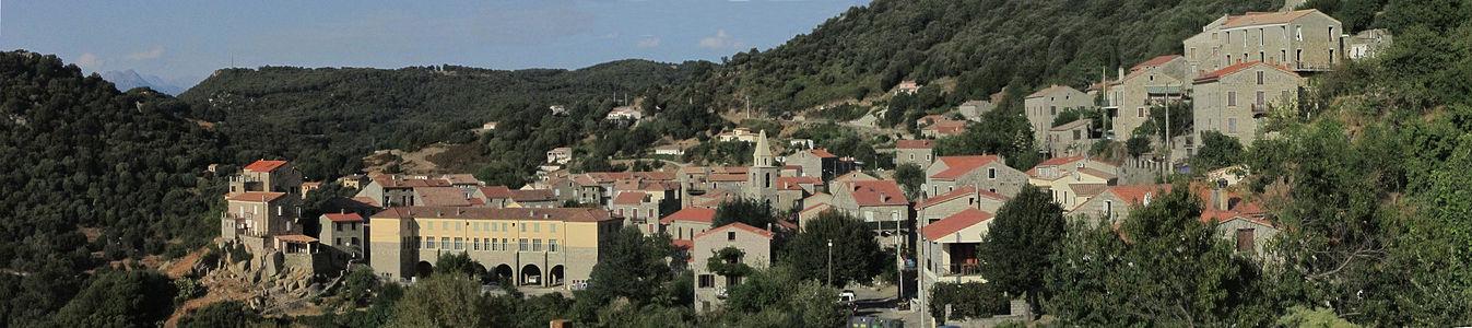 panorama d'un village de moyenne montagne, un ensemble de batiments en pierre regroupés sur un éperon rocheux.
