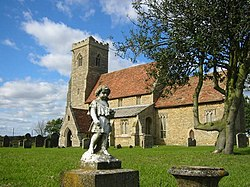 A stone church with red tiled roofs seen from an angle, the battlemented tower being on the left. In the foreground is a statue of a child.