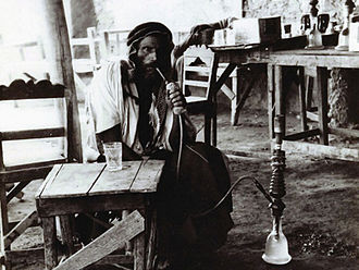 Mu'assel - Bedouin smoking a hookah, locally called nargileh, in a coffeehouse in Deir ez-Zor, on the Euphrates, 1920s
