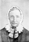 A black and white picture of an elderly woman wearing a white bonnet and dark clothing.