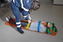 Una allieva soccorritrice della CRI si addestra ad immobilizzare un paziente su una tavola spinale