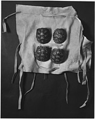 Photograph of cloth with four terrapin shell rattles to be tied around a dancer's leg