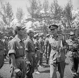 Johor - British Brigadier J J McCully inspects men of the 4th Regiment of the Malayan People's Anti-Japanese Army (MPAJA) guerrillas at Johor Bahru after the end of war against the Japanese, 1945