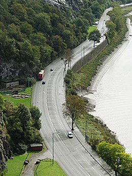 Aerial view of a road next to a river gorge, with traffic along it