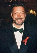 A bearded man, wearing a white shirt, black bowtie, and black jacket, smiles at the camera.